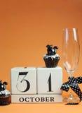 愉快的万圣夜救球日期白色块日历用香槟玻璃和巧克力松饼-与拷贝空间的垂直。 库存图片