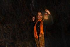 愉快的万圣夜!一个俏丽的巫婆用一个大南瓜 美丽的yo 库存照片