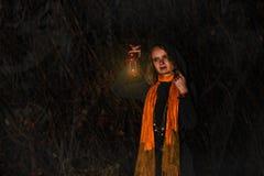 愉快的万圣夜!一个俏丽的巫婆用一个大南瓜 美丽的yo 免版税库存照片