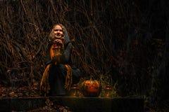 愉快的万圣夜!一个俏丽的巫婆用一个大南瓜 美丽的yo 图库摄影