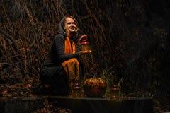 愉快的万圣夜!一个俏丽的巫婆用一个大南瓜 美丽的yo 免版税库存图片