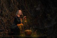 愉快的万圣夜!一个俏丽的巫婆用一个大南瓜 美丽的yo 免版税图库摄影