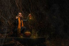 愉快的万圣夜!一个俏丽的巫婆用一个大南瓜 美丽的yo 库存图片