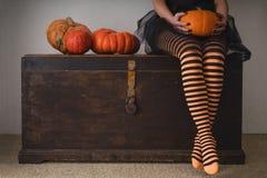 愉快的万圣夜!在长袜的女性脚用橙色南瓜 库存图片
