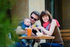 愉快的三口之家在一个室外咖啡馆 库存图片