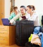愉快的三口之家在互联网上的预留的手段 免版税库存照片