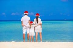 愉快的三口之家在圣诞老人帽子在期间 免版税库存图片