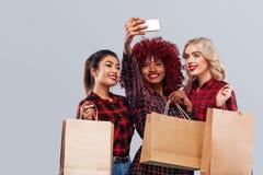 愉快的三名妇女 美国黑人,亚洲和白种人种族 购物与selfie照片射击 查出在灰色 免版税图库摄影