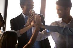 愉快的不同的企业队给成功刺激的高五 免版税图库摄影