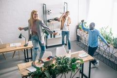 愉快的不同种族的企业同事跳舞大角度看法和在现代的有乐趣 免版税库存图片