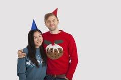 愉快的不同种族的夫妇佩带的党帽子画象在家 免版税库存图片