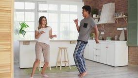 愉快的不同种族的夫妇跳舞在睡衣的厨房里 在获得的爱的有吸引力的夫妇乐趣在家 慢动作 股票录像