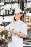 愉快的与导线的厨师混合的鸡蛋在碗扫 免版税库存照片