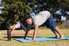 愉快的与朋友的男孩实践的瑜伽画象公园的 免版税图库摄影