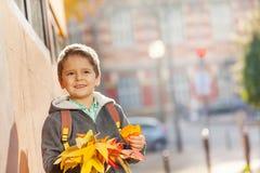 愉快的与槭树束的男小学生常设外部 图库摄影