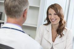 愉快的与男性医生的妇女耐心会谈在办公室 免版税库存照片