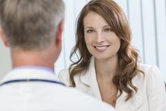 愉快的与男性医生的妇女耐心会谈在办公室 库存照片