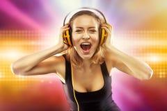 愉快的与耳机的妇女听的音乐 免版税库存照片
