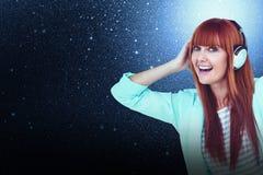 愉快的与耳机的行家妇女听的音乐的综合图象 免版税库存图片