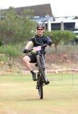 愉快的中部变老了人流行的自行车前轮离地平衡特技在终点线在Moun 库存照片