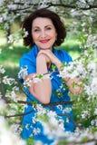 愉快的中部在庭院里变老了有开花的樱桃树的妇女 免版税库存照片