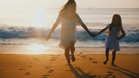 愉快的中间年迈的跑远离大波浪的母亲和小女儿一起获得乐趣在史诗日落海洋海滩 股票视频