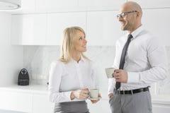 愉快的中间成人企业夫妇食用咖啡在厨房 免版税图库摄影