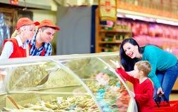 愉快的买家和卖主在杂货超级市场 免版税库存照片