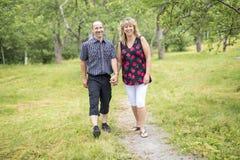 愉快的五十对前辈夫妇在公园 免版税库存图片