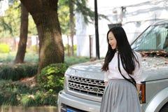 愉快的亚洲中国俏丽的女孩穿戴学生衣服在学校在春天支持一辆汽车本质上 免版税库存图片