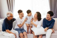 愉快的亚洲大家庭一起坐沙发,摆在为小组照片 免版税库存照片