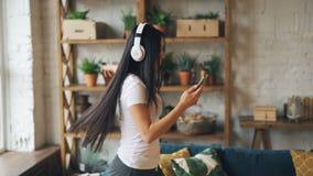 愉快的亚洲女学生佩带的耳机和听到音乐,跳舞的举行智能手机的慢动作和 股票录像