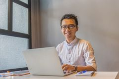 愉快的亚洲男性千福年与在膝上型计算机的玻璃工作 免版税库存图片