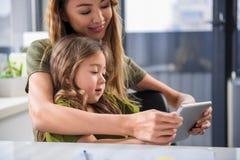 愉快的亚裔与她的孩子的妇女观看的动画片 库存图片