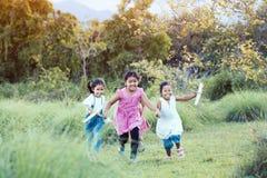 愉快的亚裔与玩具纸飞机的孩子跑和戏剧 免版税库存照片
