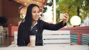 愉快的亚裔夫人与朋友网上制造的录影电话谈话使用坐在单独露天咖啡馆的智能手机 女孩是 影视素材