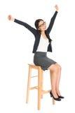 愉快的亚裔女孩坐椅子 免版税库存照片