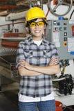 愉快的亚裔女性产业工人画象有机械的在背景中 免版税库存照片