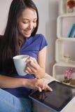 愉快的亚裔妇女坐举行杯子咖啡usi的长沙发 免版税库存照片