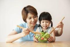 愉快的亚裔年轻烹调沙拉的母亲和女孩 免版税库存图片