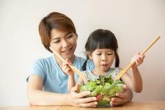 愉快的亚裔年轻烹调沙拉的母亲和小女孩 免版税库存照片