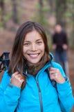愉快的亚裔徒步旅行者女孩在有背包的森林里 免版税库存图片