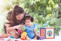 愉快的亚裔母亲和使用与玩具的女婴 免版税库存图片