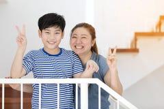 愉快的亚裔母亲和儿子在家拍照片 免版税库存照片