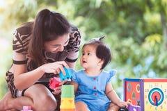 愉快的亚裔母亲和逗人喜爱的使用与玩具的女婴 库存图片