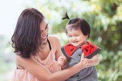 愉快的亚裔母亲和逗人喜爱的矮小的一起使用的女婴 图库摄影
