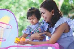 愉快的亚裔母亲和逗人喜爱的矮小的一起使用的女婴 免版税图库摄影