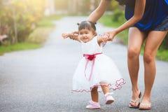 愉快的亚裔母亲和逗人喜爱的矮小的一起走的女婴 库存照片