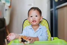 愉快的亚裔矮小的男婴坐孩子主持被弄脏室内吃的面包用被充塞的巧克力充满的点心和  库存图片