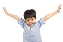 愉快的亚裔逗人喜爱的男孩延伸他的有微笑的胳膊 免版税图库摄影